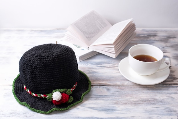 Black knitted hat with christmas decor is on a white wooden table with books and cup of tea.