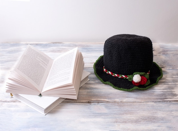 Black knitted hat with christmas decor is on a white wooden table with books.