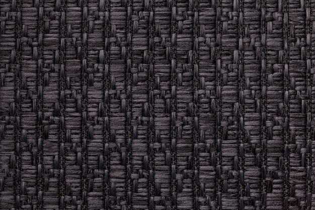 Black knitted woolen background with a pattern of soft, fleecy cloth. texture of textile closeup.