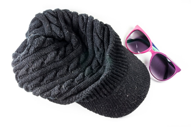 Черные вязаные шерстяные шапки и солнцезащитные очки на белом