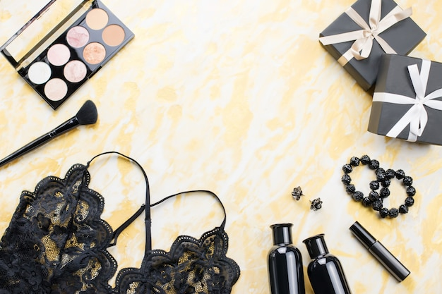 Black lace lingerie with beauty care products and gift boxes on golden table top