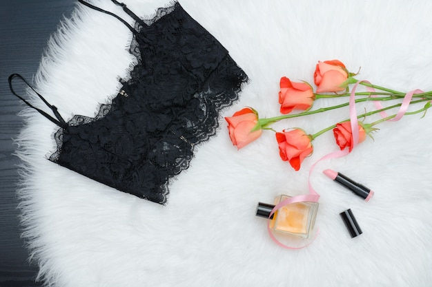 Black lace top on the white fur. orange roses, lipstick and perfume.