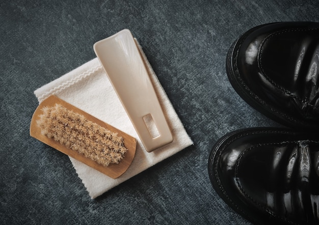 Черные лакированные туфли и набор для ухода за обувью, щетка, ложка для обуви и ткань для полировки, стилизованные