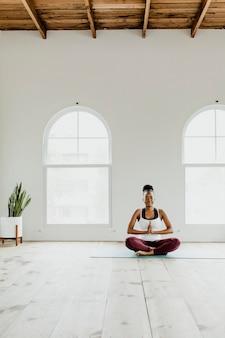 Черная женщина делает позу йоги сукхасана