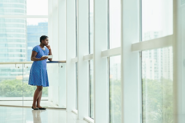 Black lady in dress with tablet leaning on handrail by office window and looking out