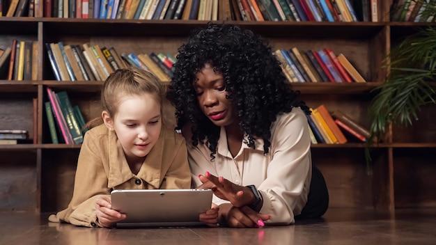 흑인 여성은 회색 태블릿을 들고 금발 여학생과 대화하고 모델 스튜디오의 책장에 기대어 나무 테이블에 앉아 있는 화면의 사진을 뒤집습니다.