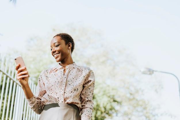Signora nera che manda un sms sul suo telefono in un parco
