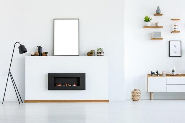 Черная лампа рядом с камином в интерьере белой гостиной с макетом пустого плаката. реальное фото