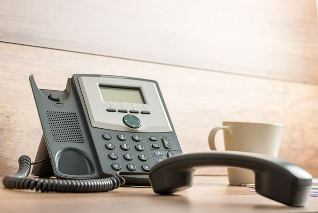 나무 사무실 책상과 그 옆에 커피 머그잔에 핸드셋이있는 검은 유선 전화