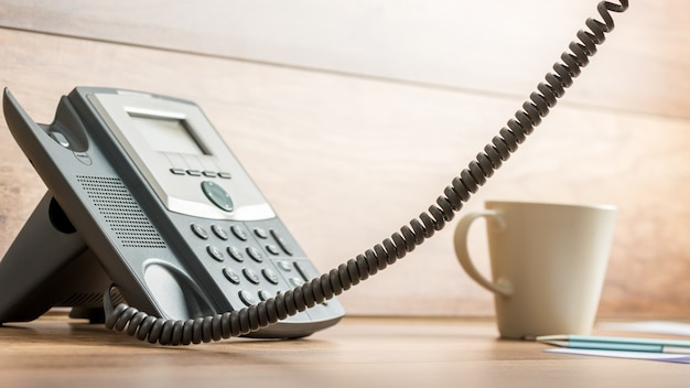 Black landline telephone with the receiver off the hook and outside the photo and coffee mug next to it on wooden office desk.