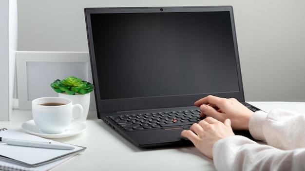黒のラップトップディスプレイモックアップブランク。白い背景の上のリモートワークの最小限のスタイルのためのホームオフィスの職場。女性はワークスペースのオンライン教育でラップトップで働いています。ノートパソコンで入力する女性の手。