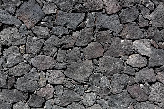 黒い溶岩石の火山の石積みの壁