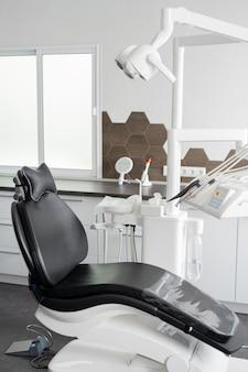 Черное кожаное кресло с медицинской лампой наверху, стоматологическое оборудование и инструменты рядом с современным стоматологическим кабинетом.