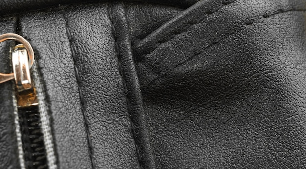 Black leather bag close-up with texture detailed surface, the seams background