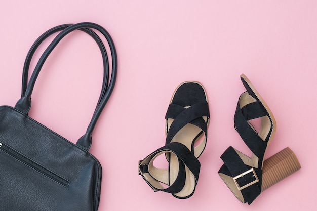 Black leather bag and fashionable summer women's shoes on pink surface