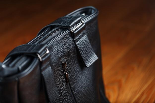 나무 배경에 손수 만든 검은 가죽 가방 수 제, 천연 재료입니다.