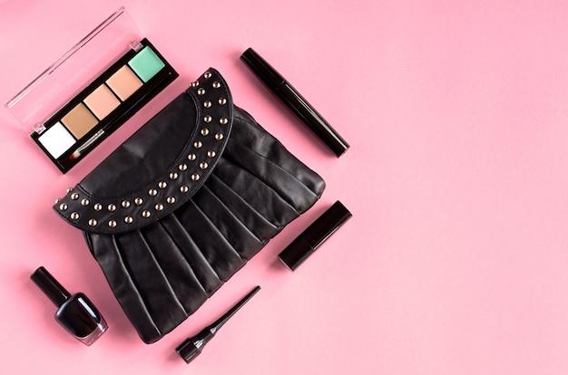 Black leather bag with nail polish, pomade, mascara and eye shadows on pink surface.