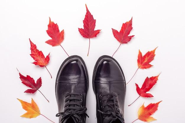 白い背景の上の黒い革のブーツと赤い葉
