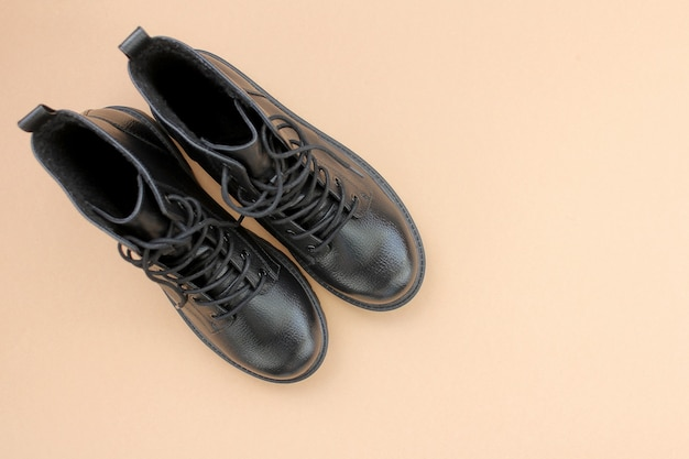 Black leather boots on brown background. fashionable modern female shoes military style.