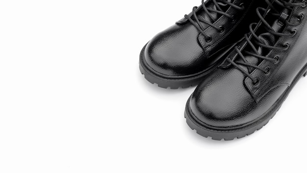 Black leather boots on white surface. fashionable modern female shoes military style. Premium Photo