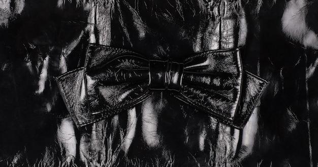 黒の背景に分離された黒革の蝶ネクタイ