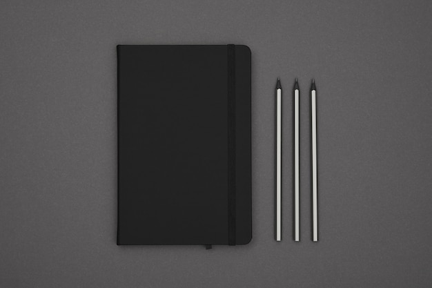 Black leather cover notebook flat lay over grey