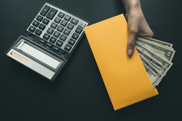 On the black leather desk a calculator, the girl holds in her hand a yellow envelope with money