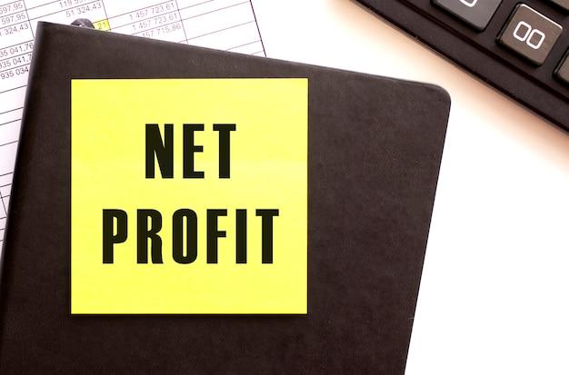 碑文と色のステッカーが付いている黒い革のノート。財務コンセプト。