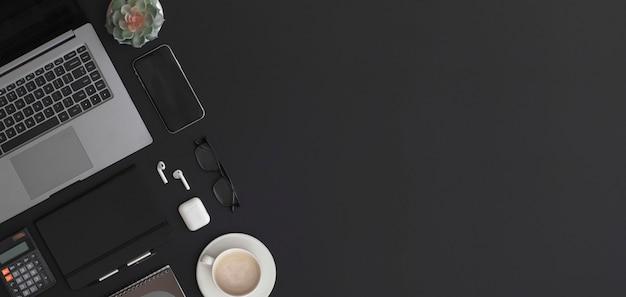 電卓ラップトップノートブックコーヒーカップと緑の植物と黒革のオフィステーブル