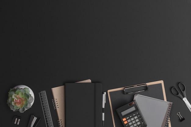 電卓、ノートブック、緑の植物と黒革のオフィステーブル。コピースペースのある上面図。フラットレイ構成。