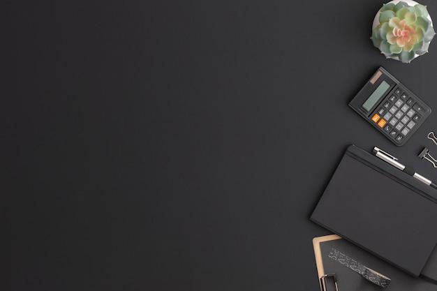 電卓、ノートブック、緑の植物と黒革のオフィステーブル。コピースペースのある上面図