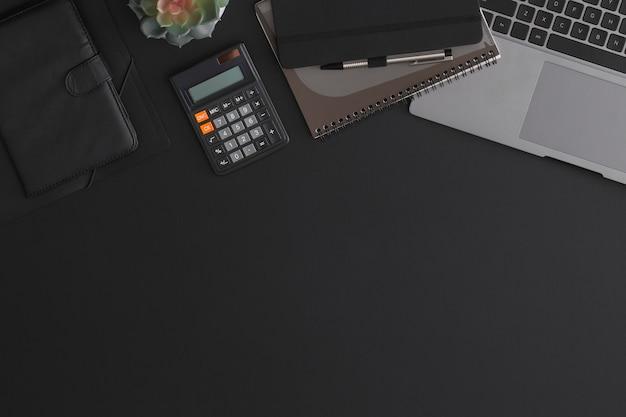 계산기, 노트북 및 녹색 식물 블랙 가죽 사무실 테이블. 복사 공간이있는 평면도