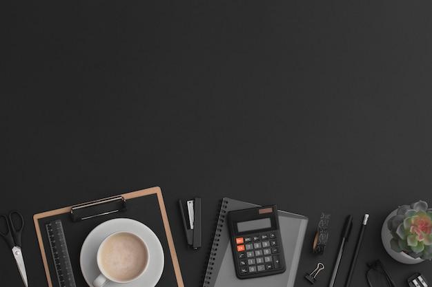 電卓、ノートブック、コーヒーカップ、緑の植物と黒革のオフィステーブル。コピースペースのある上面図。フラットレイ構成。