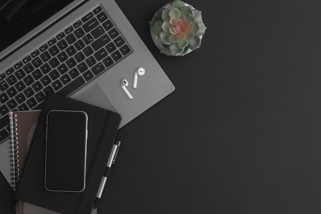 電卓ノートブックコーヒーカップと緑の植物と黒革のオフィステーブル