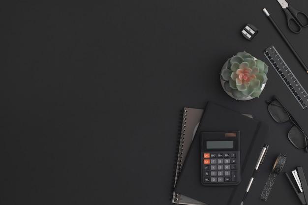 電卓、ノートブック、文房具、緑の植物と黒革のオフィステーブル。コピースペースのある上面図。フラットレイ構成。