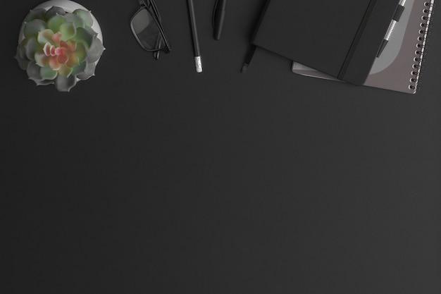 ノートブックと緑の植物と黒革のオフィステーブル。コピースペースのある上面図。フラットレイ構成。