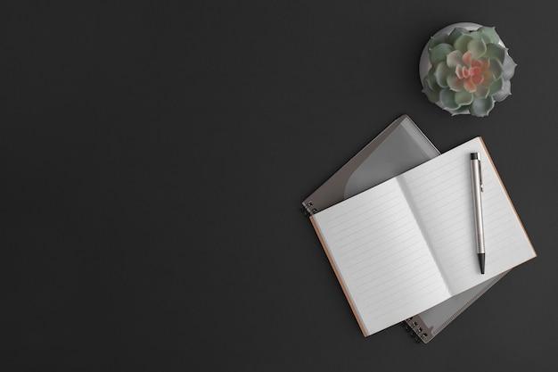 ノートブック、ペン、緑の植物と黒革のオフィステーブル。コピースペースのある上面図。フラットレイ構成。