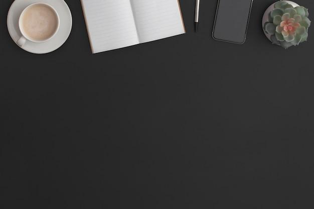ノートブック、ペン、緑の植物、コーヒーカップ、スマートフォンを備えた黒革のオフィステーブル。コピースペースのある上面図。フラットレイ構成。