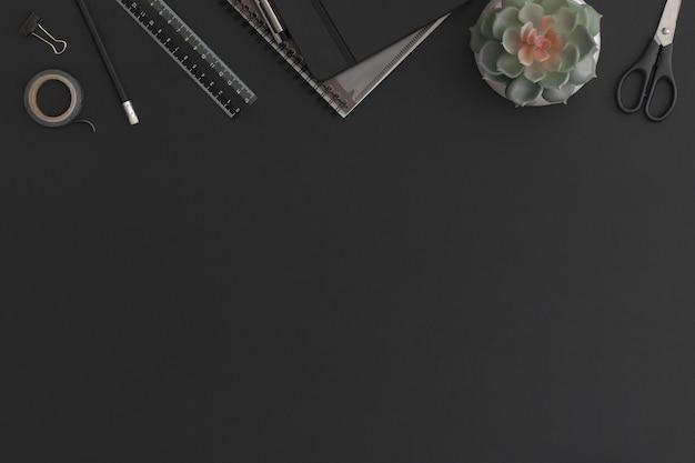 ノートブック、文房具、緑の植物と黒革のオフィステーブル。コピースペースのある上面図。フラットレイ構成。