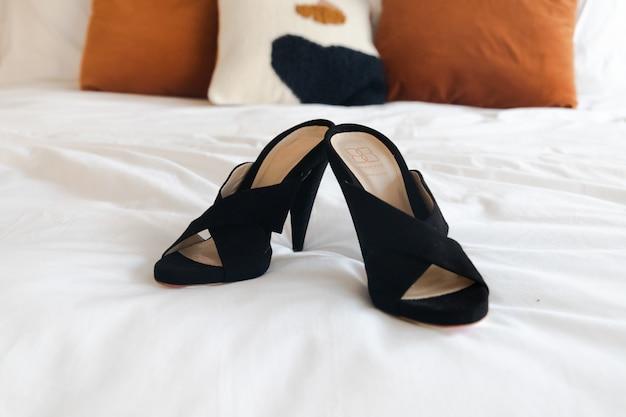 Black leather peep-toe heeled sandals on white bed