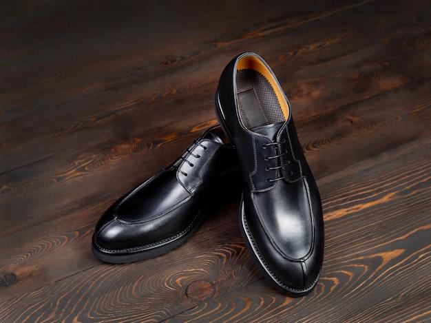 어두운 버려진 보드에서 나무 배경에 클래식 컷의 검은 가죽 신발