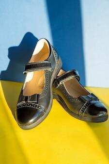 밝고 화려한 배경의 검은색 가죽 신발. 새 가죽 소녀 신발, 학교로 돌아갈 준비