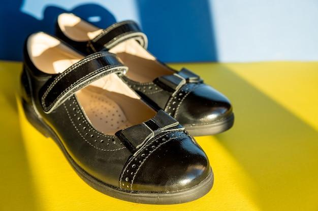 밝고 화려한 배경의 검은색 가죽 신발. 새 가죽 여학생 신발, 학교 개념으로 돌아갈 준비를 합니다. 교복입니다. 공간 복사