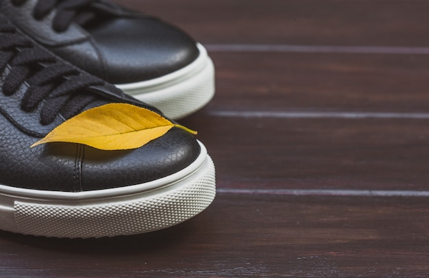 Black leather sneakers with yellow leaf on wooden background. fall concept