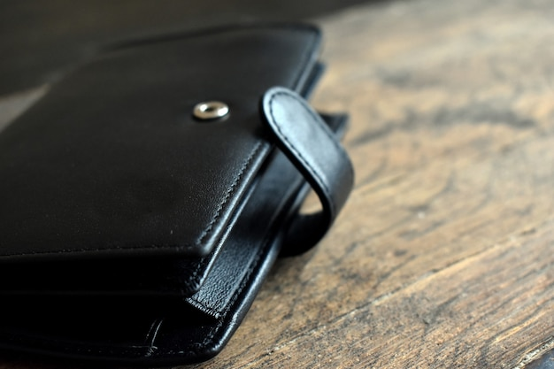 Black leather wallet on a light wooden background
