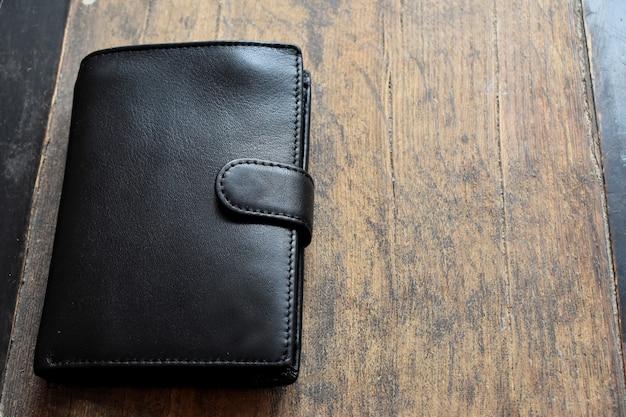 明るい木製の背景に黒い革の財布