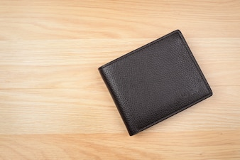 Black leather wallet on wooden background