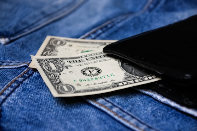 Black leather wallet with money on back blue jeans pocket denim texture.
