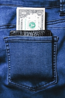 Black leather wallet with money in back blue jeans pocket denim texture.