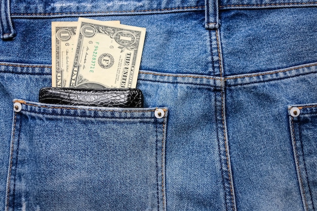 Black leather wallet with money in back blue jeans pocket denim